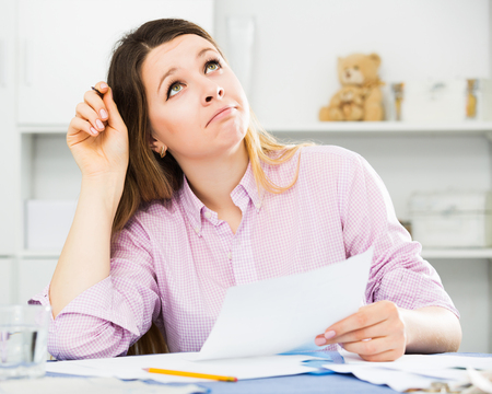 Girl signing agreement papers of financial nature at home