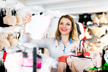 Positive female customer deciding on pretty clothing in underwear shop Stock Photo