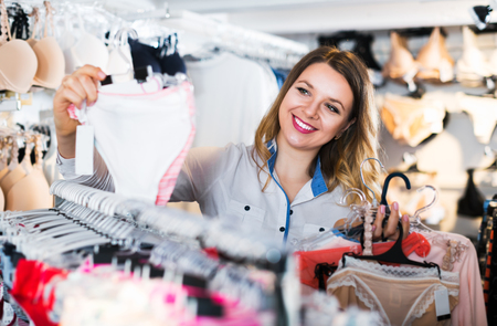 Young woman choosing pretty clothing in lingerie store