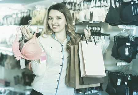 Glad pleasant  female shopper boasting her purchases in underwear shop Stock Photo