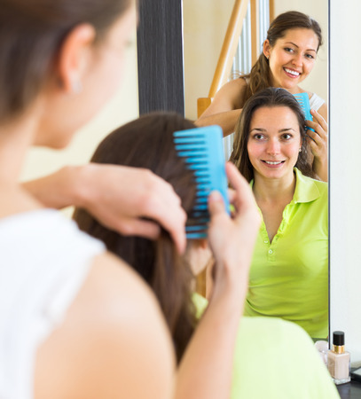 Cheerful young woman brushing her friend in front of the mirror at home