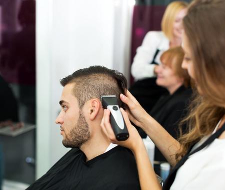 Young man cuts hair at the hair salon