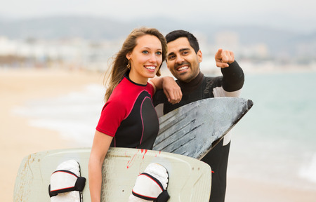 Young smiling active couple resting on the beach with surf boards. Focus on girl Stock Photo