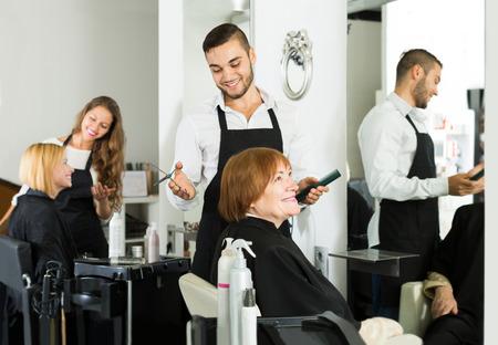 peignoir: happy european barber makes the cut for mature woman Stock Photo