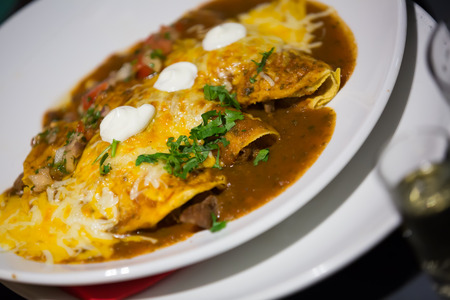 Traditional enchilada corn tortilla with chili pepper sauce in restaurant