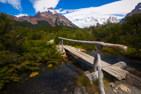 Bridge over creek on pathway at foot of Andes mountains. Patagonia, Argentina, Chile, Andes Stock Photo