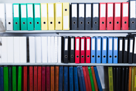 Many folders standing on shelfs in the store Stock Photo