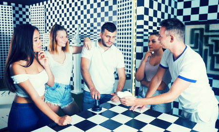 Group of smiling adults standing near chessboard in quest room and solving conundrum
