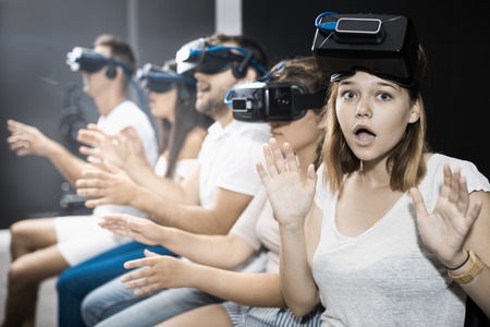 avocation: Agitated young girl experiencing with friends virtual reality
