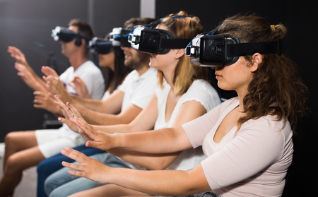 avocation: Young american girl with friends wearing VR headset, interactive touching over air