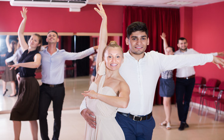 Smiling young people dancing samba in pairs in dance class