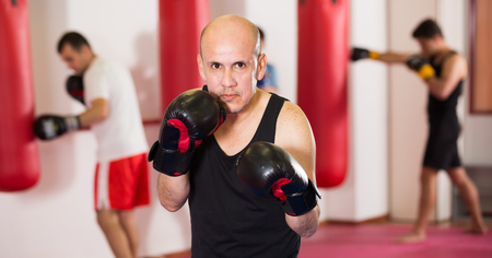 adult sportsman in the boxing hall practicing boxing punches during training