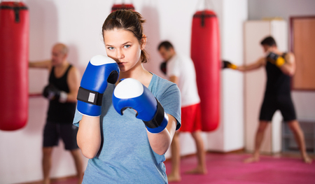 Portrait of young positive female sportswear training in colored boxing gloves