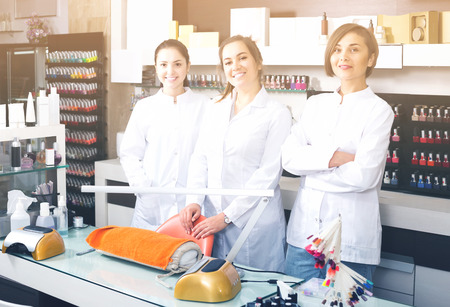 Portrait of happy russian professional manicurists at working place inviting to salon