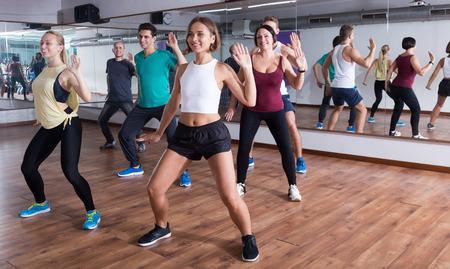 Young happy people dancing zumba elements in dancing class