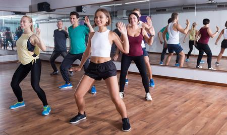 Young happy people dancing zumba elements in dancing class