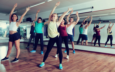 Positive people exercising zumba elements together in dancing class