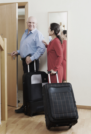 Senior man and Mature girl with suitcases near door at home photo