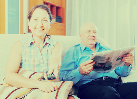 Portrait of  mature woman with TV remote against elderly man with newspaper in home interior photo