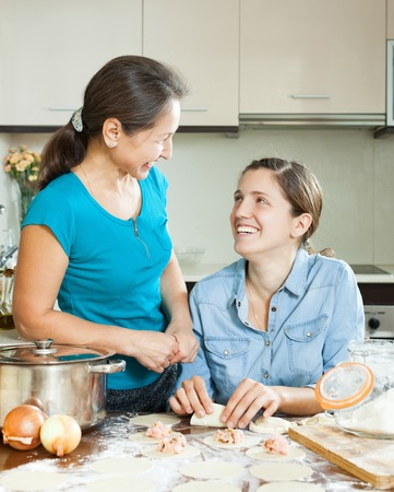 women cooking meat dumplings together at home photo