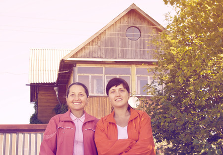 Outdoor portrait of two happy women against real estate photo