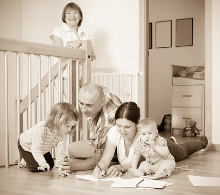 Ordinary multigeneration family with  children  on floor at home photo