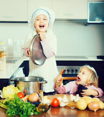 Two cheerful little sisters with pot smiling at home kitchen photo