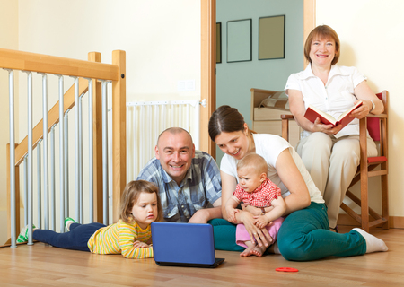 Happy friendly family of three generations with laptop  in living room at home photo