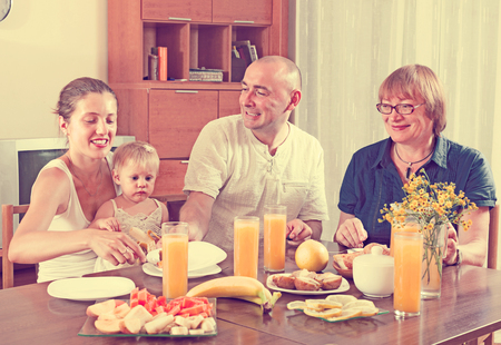 Portrait of happy multigeneration family  eating friuts with juice at home together photo