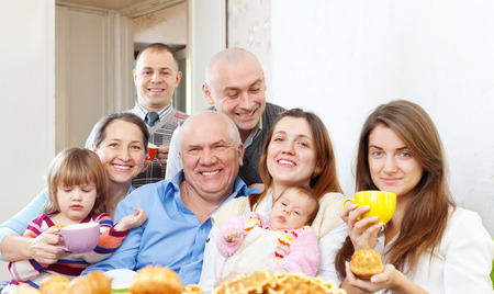 large happy multigeneration family family drinks tea with baked at home photo