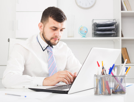 expertize: Smiling man worker working effectively on project in office