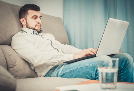 Depressed young male spending day alone at home Stock Photo