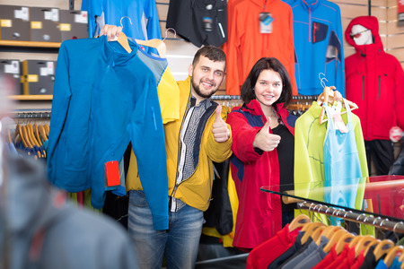 boasting: Young couple boasting various sportswear items in sports clothes store