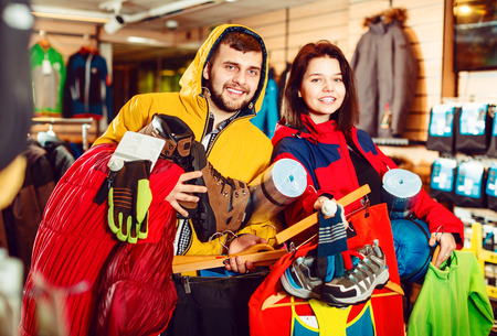 Man and woman demonstration new tourist equipment in sports clothes store