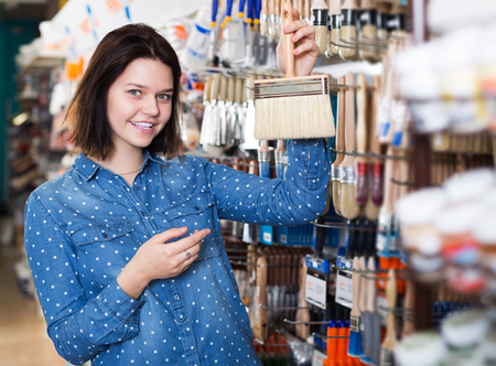 Young woman choosing brush for house decoration in paint supplies store Stock Photo