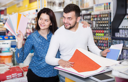 coatings: Smiling couple examining a various decorative materials in a paint supplies store. Focus on both persons Stock Photo