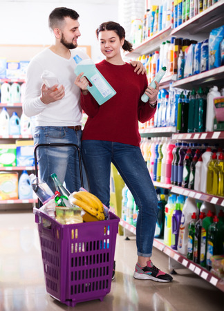 two adult people in good spirits selecting detergents ?n the shelves in the store Stock Photo
