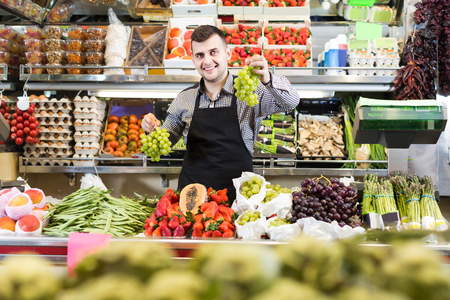 happy russian male shopping assistant weighing grapes in grocery shop