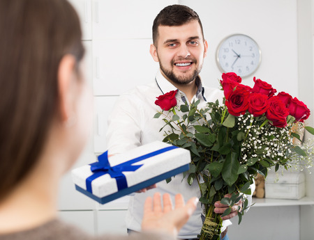 Guy congratulating woman with bouquet and gift for romantic dinner Stock Photo