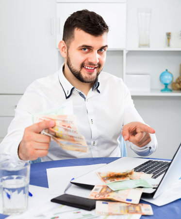 expertize: Young happy cheerful positive male businessman earning money easily online in Internet