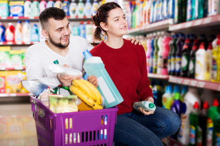 Cheerful people buying detergents for house in the shopping mall