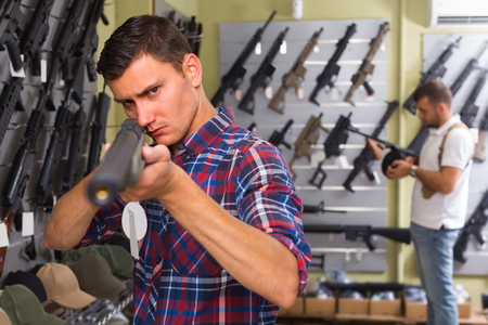 Portrait of man 20-30 years old which is choosing air-powered gun in army market.
