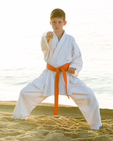 Young boy training karate positions at ocean quay