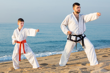 Positive adult man and boy exercising karate in morning outdoor