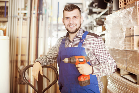 owning: Positive builder male demonstrating various tools at workshop Stock Photo