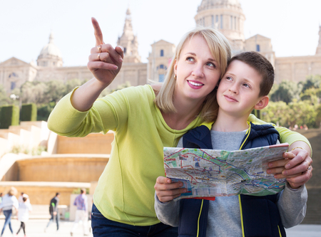 attachment: Positive young mother and son reading map guide during sightseeing tour