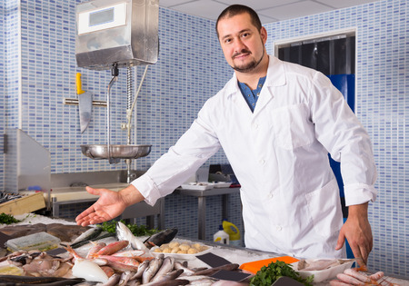Adult friendly man with beard arms folded standing near fish counter