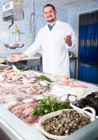 Adult male  with beard arms folded standing near fish counter