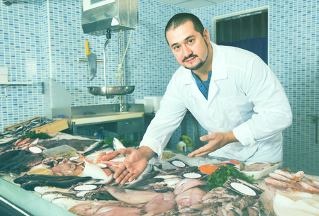 Cheerful positive man in white cover-slut showing fish on counter