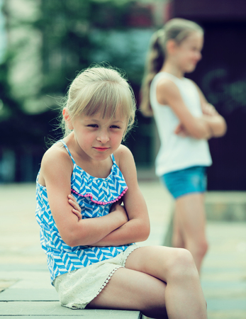 Two quarreled little girls having problems in relationship